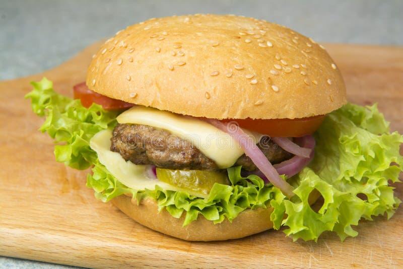 Cheeseburger z sałatą, pomidorem i cebulą na brioche babeczce, zdjęcie stock