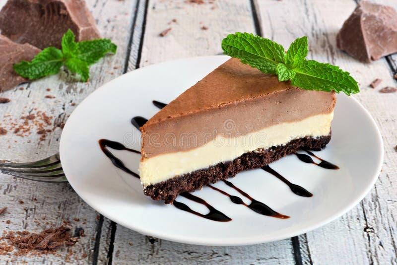 Cheesecake βανίλιας σοκολάτας ενάντια στο αγροτικό άσπρο ξύλο στοκ εικόνες με δικαίωμα ελεύθερης χρήσης
