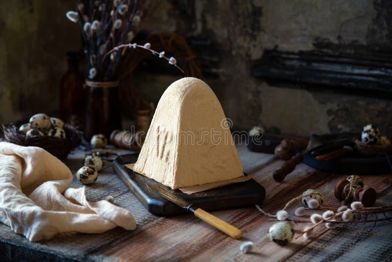 Cheesecake εξοχικών σπιτιών Πάσχας καραμέλας που στέκεται στον ξύλινο πίνακα στον γκρίζο ξύλινο πίνακα στοκ εικόνες
