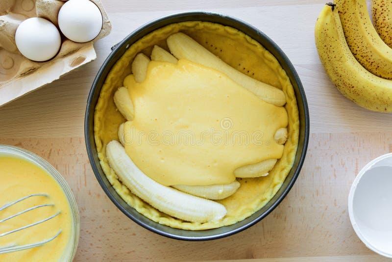 Cheesecake κέικ μπανανών προετοιμασιών που κάνει από τα συστατικά στο ξύλινο επιτραπέζιο υπόβαθρο Επίπεδος βάλτε Τοπ όψη στοκ εικόνα