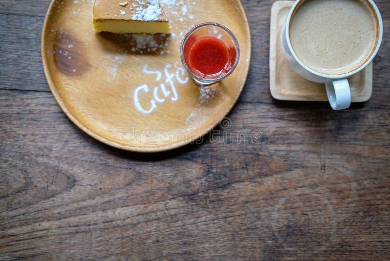 cheesecake με τη ζάχαρη καλύμματος & τήξης σάλτσας φραουλών καυτό capp στοκ εικόνες