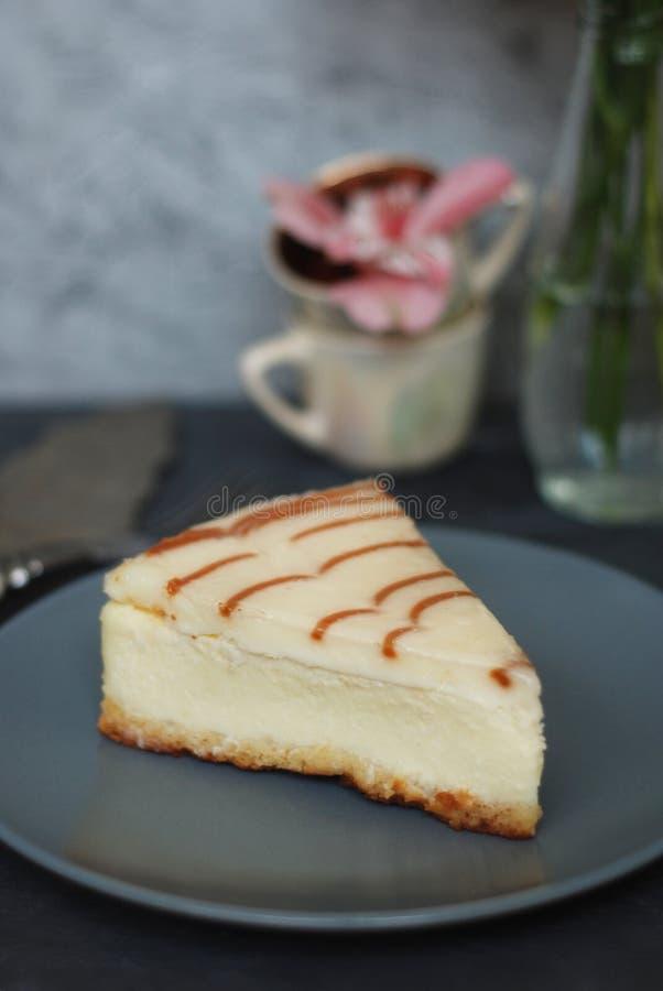 Cheesecake με τη σάλτσα καραμέλας σάλτσας καραμέλας πέρα από το καφετί έγγραφο με το γλυκό επιδόρπιο ζάχαρης κουταλιών στοκ εικόνα με δικαίωμα ελεύθερης χρήσης