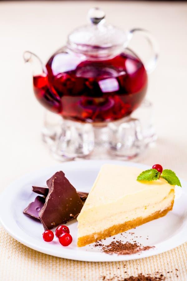 Cheesecake που διακοσμείται με τα κομμάτια σοκολάτας, τα φύλλα των βακκίνιων και μεντών και teapot γυαλιού στοκ φωτογραφία με δικαίωμα ελεύθερης χρήσης