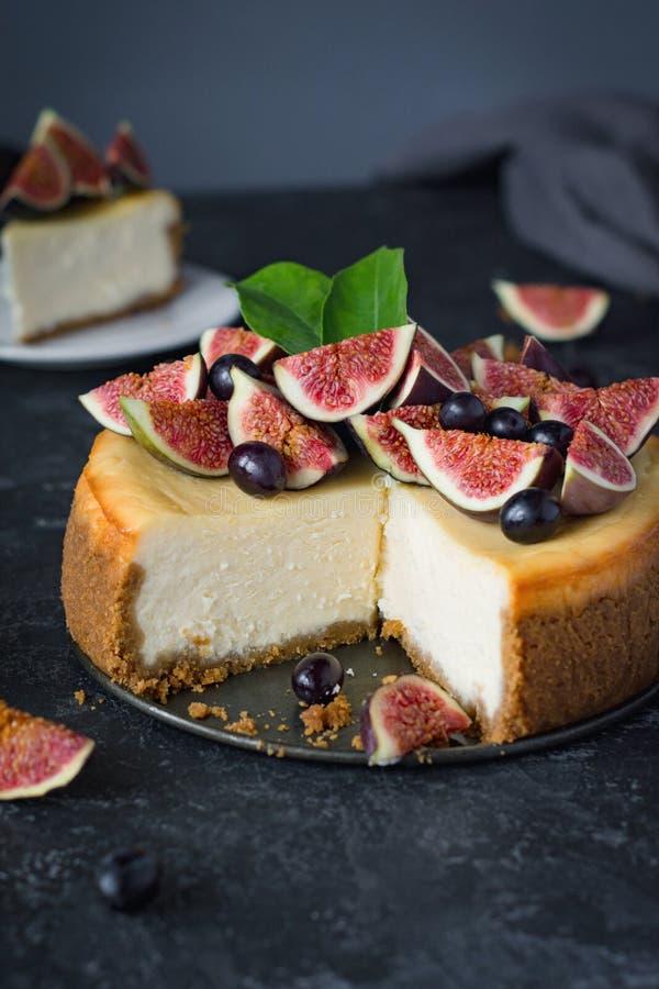Cheesecake της Νέας Υόρκης που ολοκληρώνεται με τα φρέσκα σύκα και τα σταφύλια στοκ εικόνες