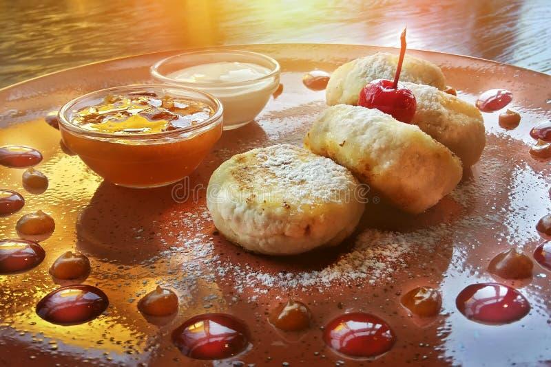 Cheesecake, φρέσκες μαρμελάδα και μέντα Οι τηγανίτες τυριών εξοχικών σπιτιών ή fritters στάρπης που διακοσμήθηκαν κονιοποίησαν τη στοκ εικόνα