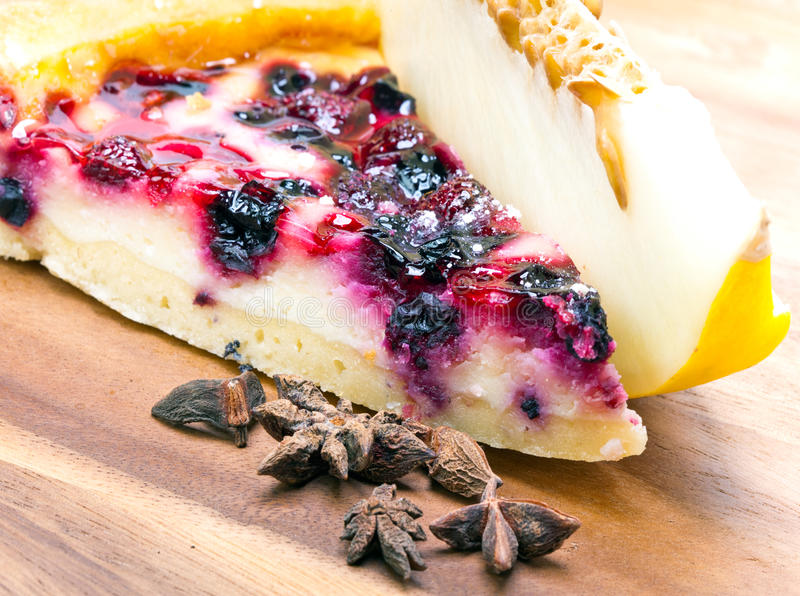 Cheesecake with berries and a fresh melon on a wooden tray royalty free stock photo