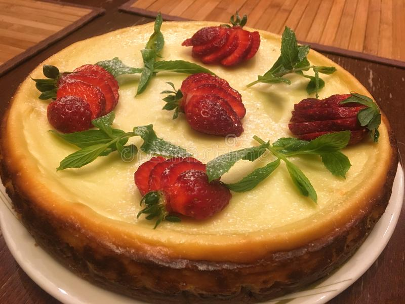 Cheesecake cake decorated with mint leaves and strawberries stock images