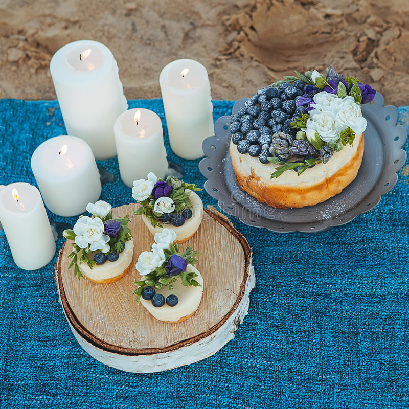 Cheesecake and capcakes decorated by blueberries and flowers on the sand. Concept date,proposal, picnic. Natural food stock photo