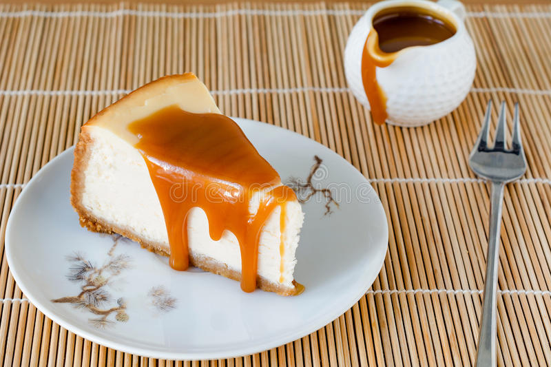 Cheesecake with caramel sauce. On white plate royalty free stock photography