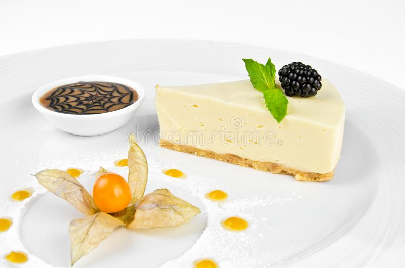 Cheesecake with chocolate cream, blackberries, mint and winter cherry royalty free stock images