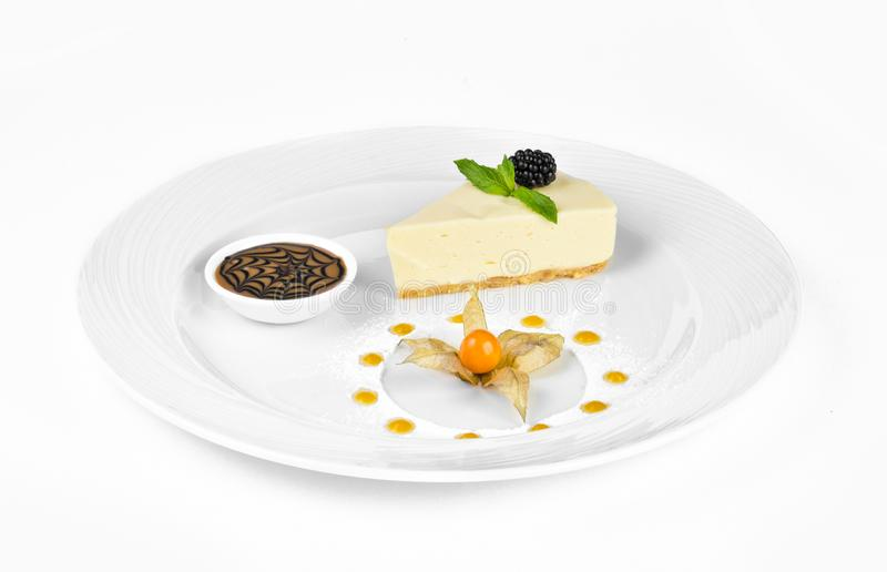 Cheesecake with chocolate cream, blackberries, mint and winter cherry royalty free stock photography