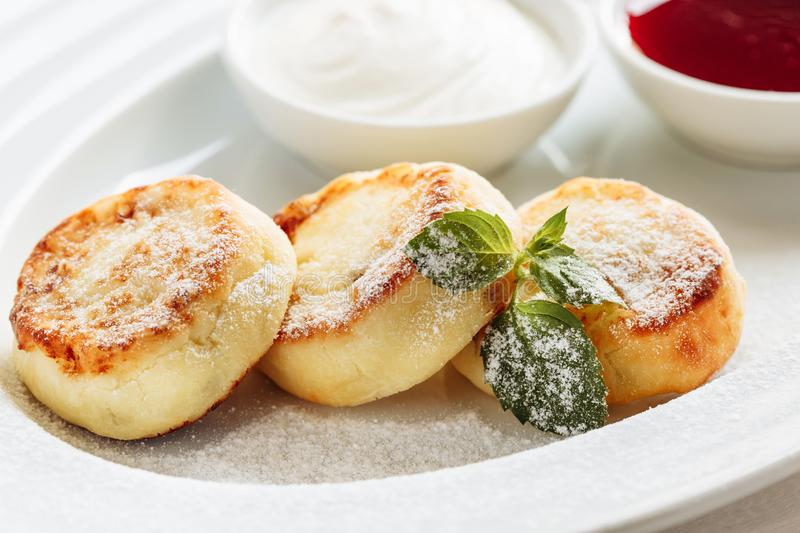 Cheesecake, fresh jam and mint. Cottage cheese pancakes or curd fritters decorated powdered sugar in plate close view stock photos