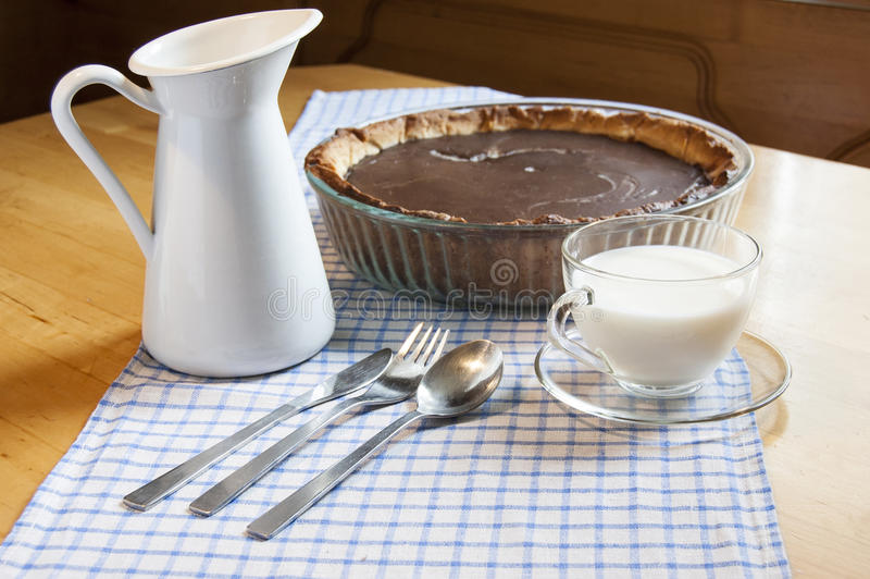 Cheesecake in a glass baking dish and milk jug. Chocolate cheesecake in a glass baking dish. Near glass cup of milk, knife, fork, spoon and milk jug stock image