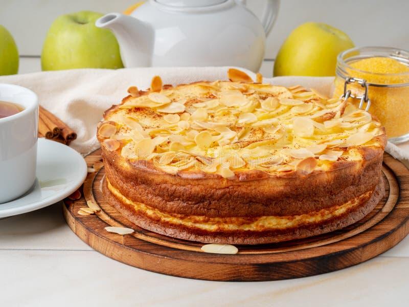 Cheesecake, jabłczany kulebiak, curd deser z polentą, jabłka, migdałowi płatki i cynamon na bielu marmuru kuchennym stole, boczny zdjęcia stock