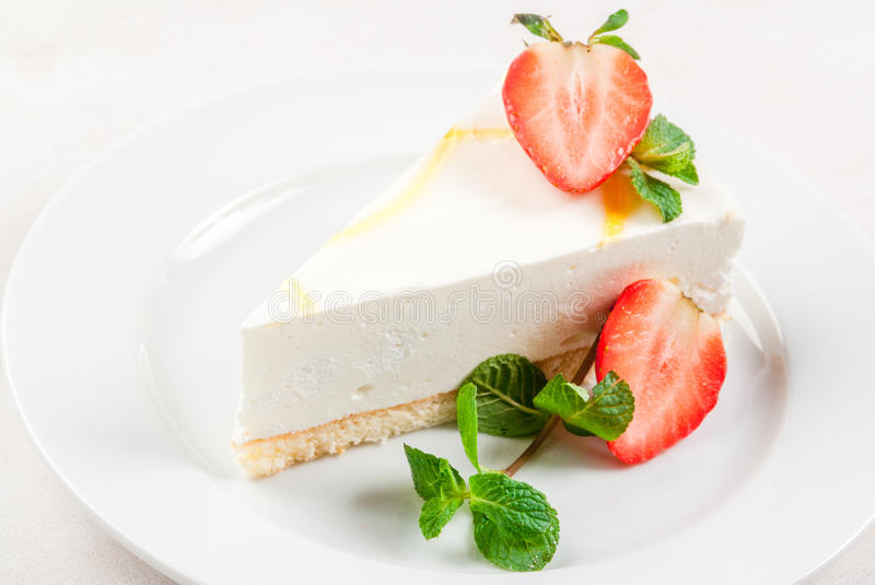 Cheesecake with mint and strawberries. Light dessert: classic cheesecake, decorated with mint and strawberries. On a white plate, on a white wooden table. Close stock photo