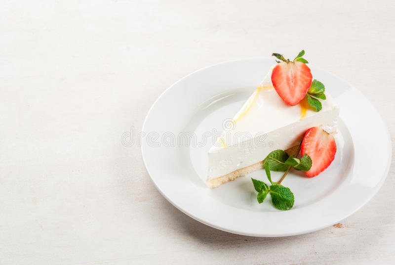 Cheesecake with mint and strawberries. Light dessert: classic cheesecake, decorated with mint and strawberries. On a white plate, on a white wooden table. Close stock photography
