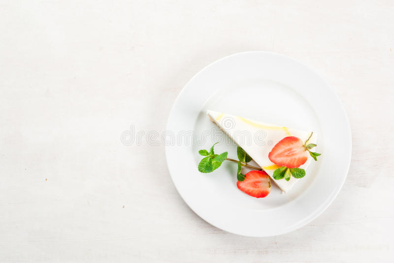 Cheesecake with mint and strawberries. Light dessert: classic cheesecake, decorated with mint and strawberries. On a white plate, on a white wooden table. Copy royalty free stock photography