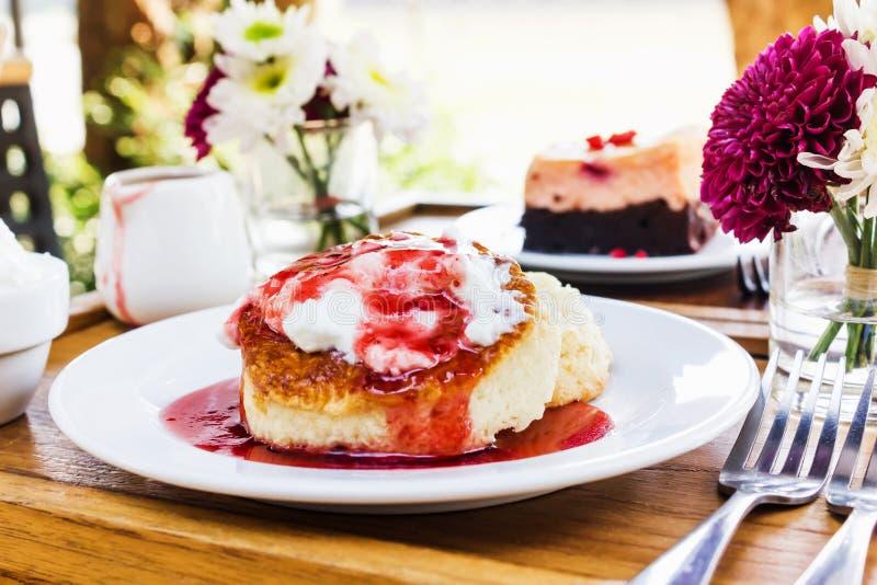 Cheesecake nakrywa truskawkowego dżem na drewnianym stole pod drzewny sh zdjęcia stock