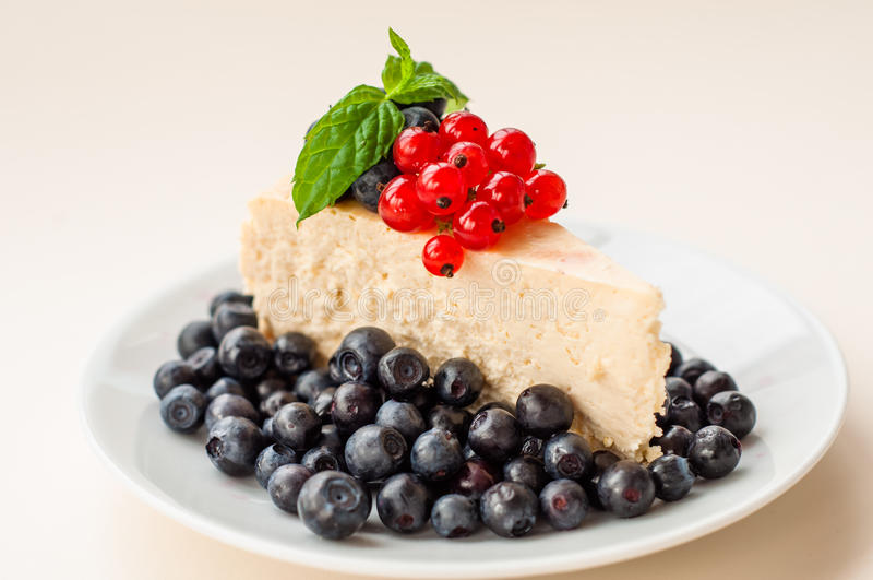Cheesecake New - York decorated with blueberries, red currants and mint royalty free stock image