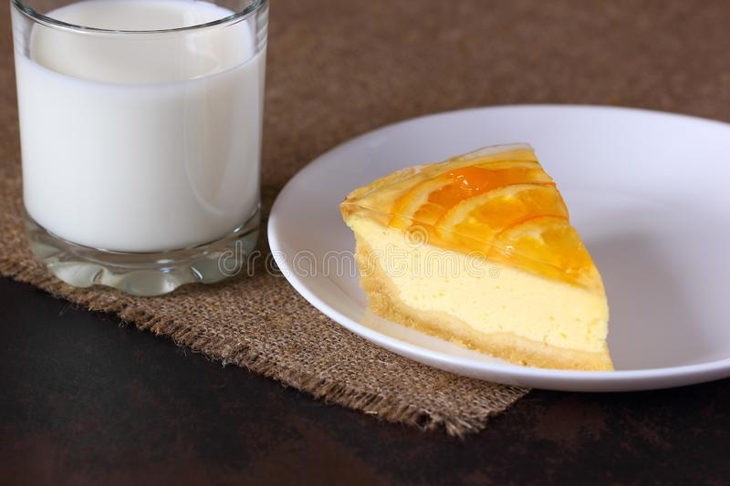 Cheesecake with oranges on a white plate, glass with milk on burlap tablecloth stock image