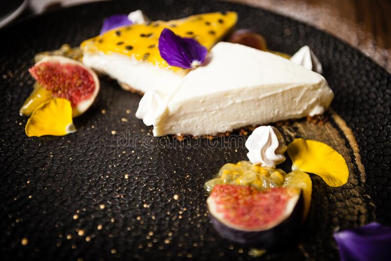 Cheesecake with passionfruit served on a plate in restaurant royalty free stock image