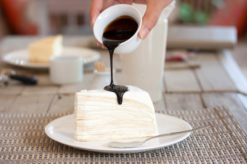 Cheesecake. Pour chocolate sauce into cheesecake royalty free stock image