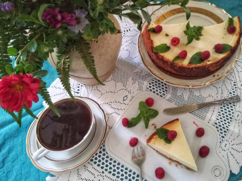 Cheesecake with raspberries and mint leaves on a beautifully served table. Cheesecake with raspberries and mint leaves on a beautifully decorated table with a royalty free stock photo