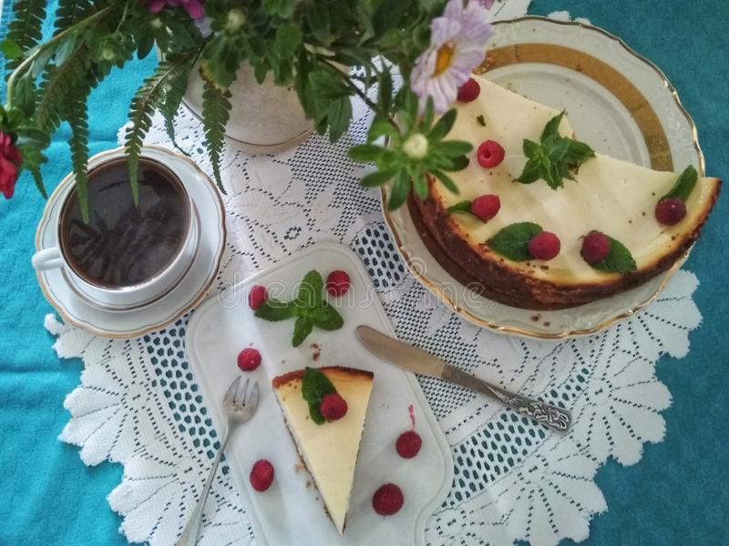 Cheesecake with raspberries and mint leaves on a beautifully served table. Cheesecake with raspberries and mint leaves on a beautifully decorated table with a royalty free stock photography