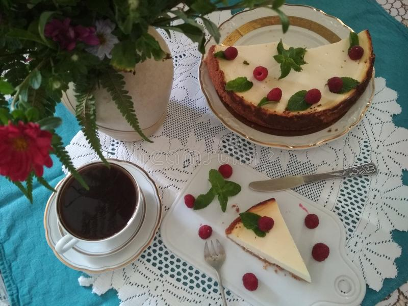 Cheesecake with raspberries and mint leaves on a beautifully served table. Cheesecake with raspberries and mint leaves on a beautifully decorated table with a stock images