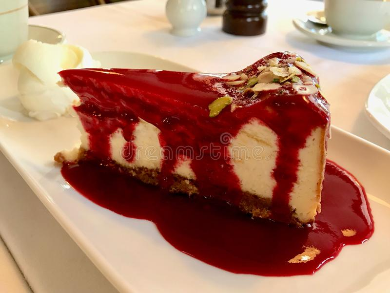 Cheesecake Slice with Blackberry Sauce served with Vanilla Ice Cream at Restaurant. Traditional Dessert royalty free stock photo