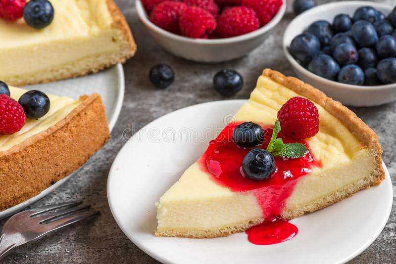 Cheesecake with slice of cake with fresh raspberries, blueberries, jam and mint on concrete background. close up stock photos