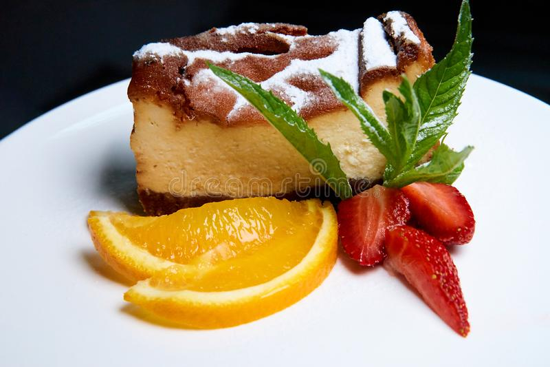 Cheesecake with strawberries and orange slices on a white dish stock image