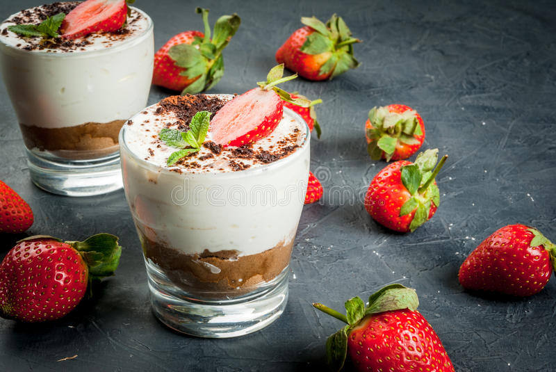 Cheesecake with strawberry and mint. Summer dessert, classic cheesecake with strawberries decorated with mint leaves. On a dark gray stone or concrete table royalty free stock photo