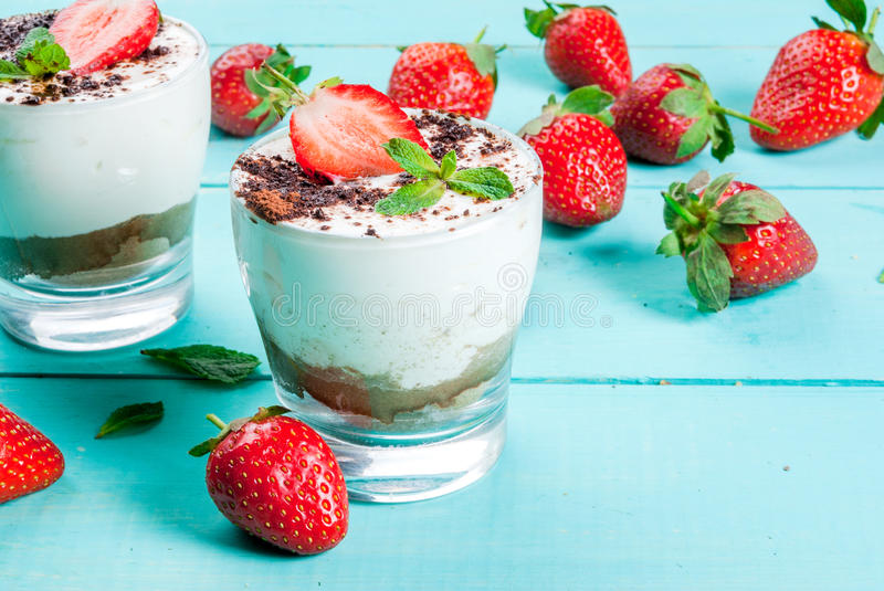 Cheesecake with strawberry and mint. Summer dessert, classic cheesecake with strawberries decorated with mint leaves. On a light blue wooden table, bright stock images