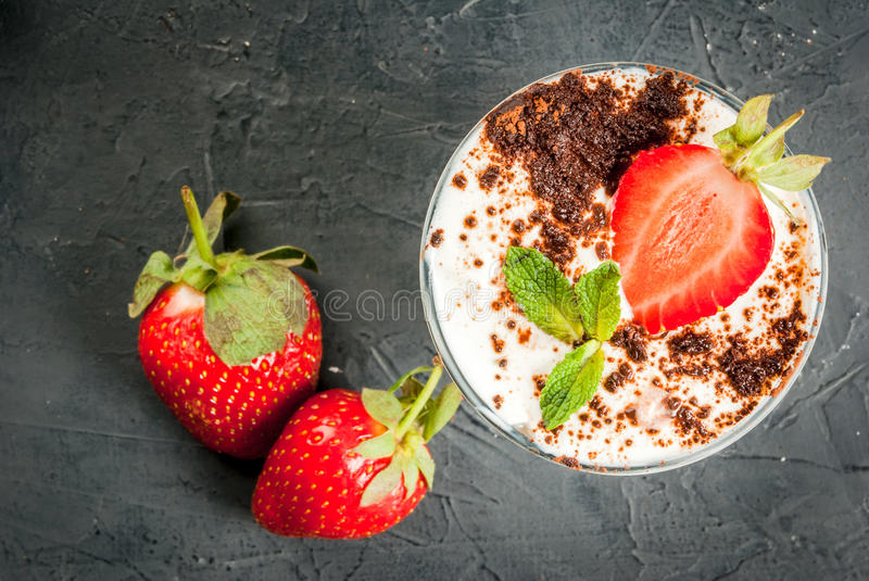 Cheesecake with strawberry and mint. Summer dessert, classic cheesecake with strawberries decorated with mint leaves. n dark gray stone table. Copy space royalty free stock photo