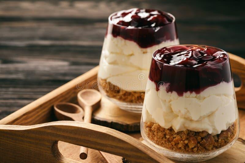 Cheesecake z wiśni galaretą w szklanych słojach obraz stock