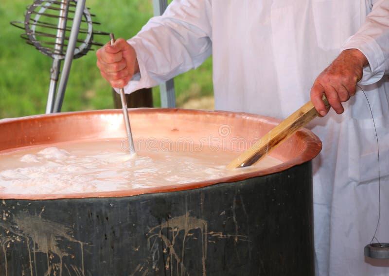 Cheesemaker sprawdza temperaturę wrzący mleko w po fotografia royalty free