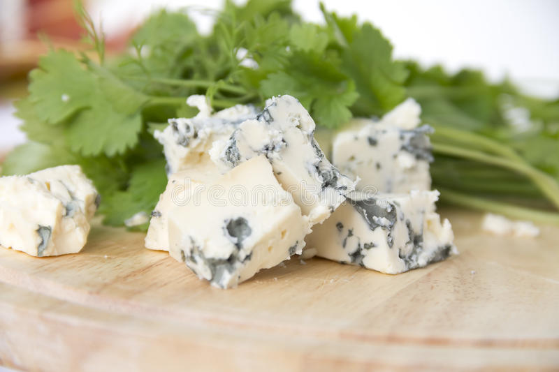 Cheeses with blue mold. Pieces of blue cheese and herbs stock photo