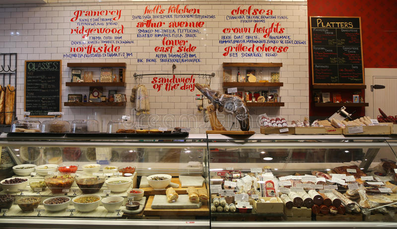Cheeses, cold cuts and pickles on display in Gramercy Park deli. NEW YORK - MAY 7, 2015: Cheeses, cold cuts and pickles on display in Gramercy Park deli royalty free stock image