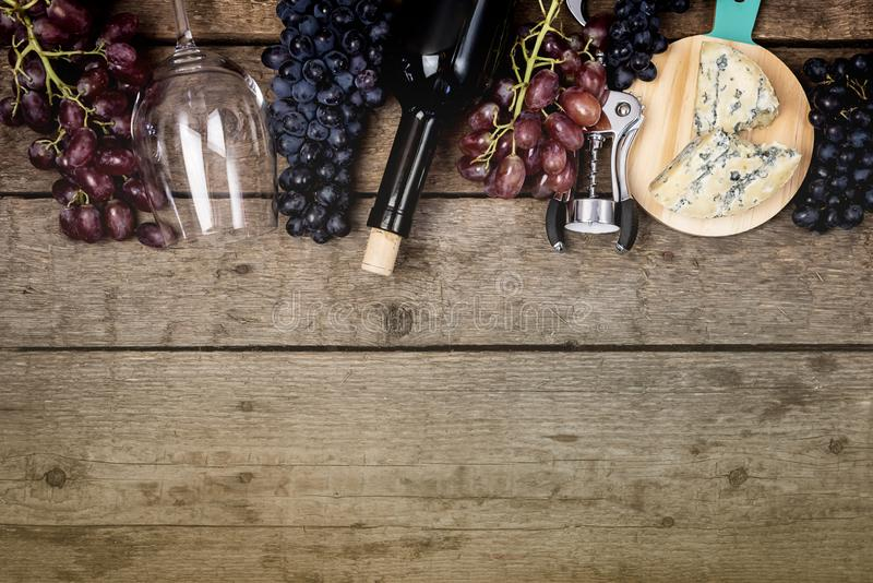 Cheeses on Wooden Board Bottle of Wine Wine Glass Ripe Grape on a Wooden Background Top view Flat Lay Copy Space Wine Background. Wine Food Concept Horizontal royalty free stock image