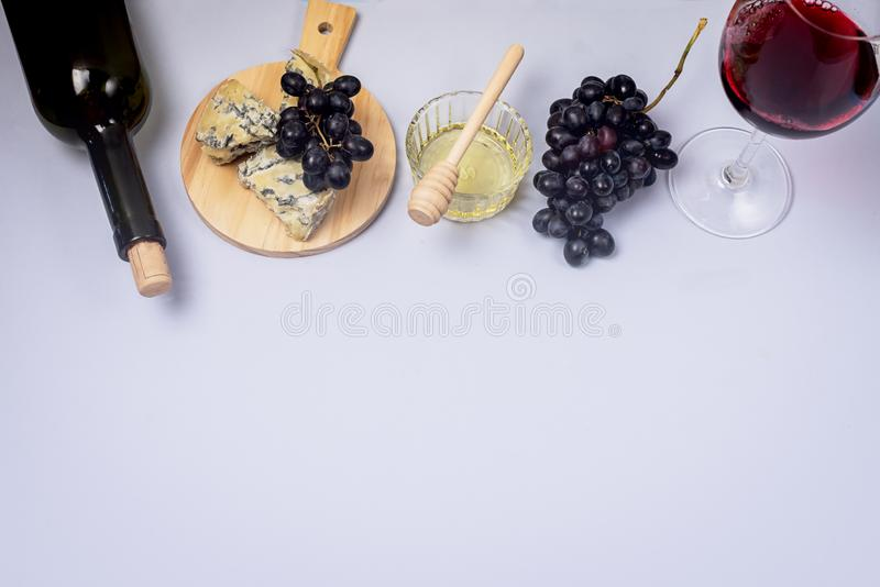 Cheeses on Wooden Board Bottle of Wine Honey Ripe Grape on a Blue Background Top view Flat Lay Copy Space Wine Background Wine. Food Concept Horizontal royalty free stock photography