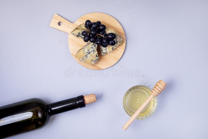 Cheeses on Wooden Board Bottle of Wine Honey Ripe Grape on a Blue Background Top view Flat Lay Copy Space Wine Background Wine. Food Concept Horizontal stock image