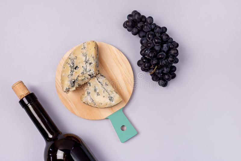 Cheeses on Wooden Board Bottle of Wine Ripe Grape on a Blue Background Top view Flat Lay Copy Space Wine Background Wine Food. Concept Horizontal stock photo