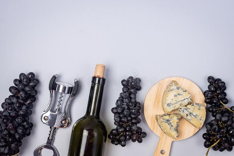 Cheeses on Wooden Board Bottle of Wine Ripe Grape on a Blue Background Top view Flat Lay Copy Space Wine Background Wine Food stock photo