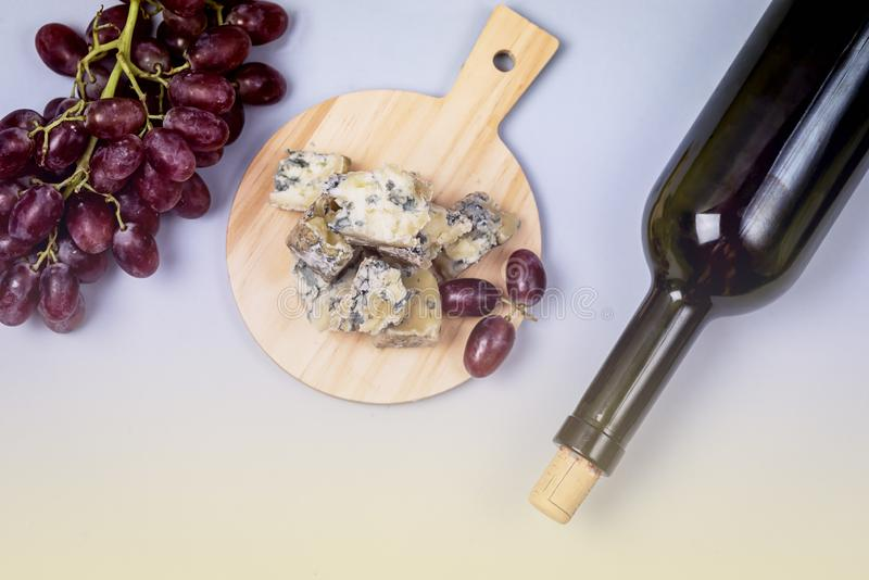 Cheeses on Wooden Board Bottle of Wine Ripe Grape on a Blue Background Top view Flat Lay Copy Space Wine Background Wine Food. Concept Horizontal Toned royalty free stock photo