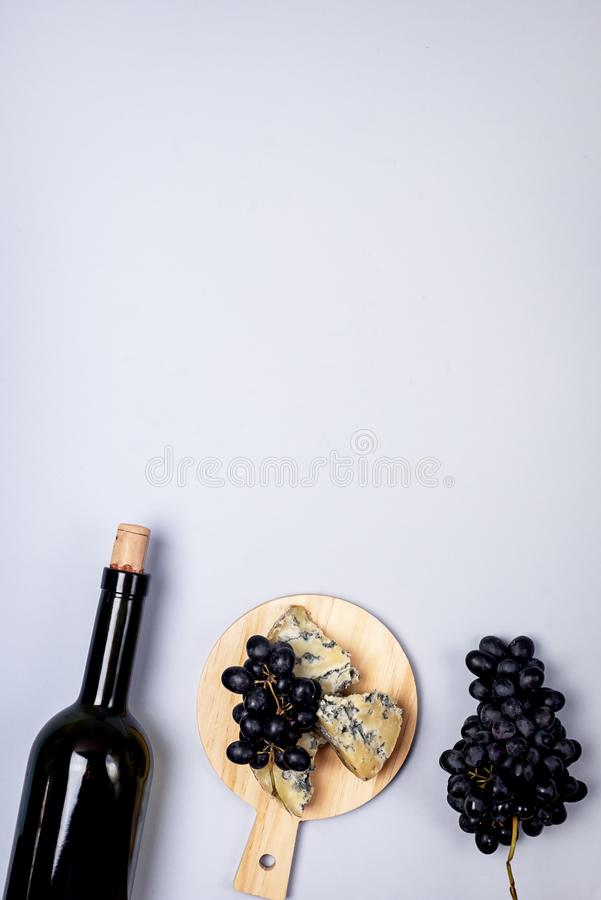 Cheeses on Wooden Board Bottle of Wine Ripe Grape on a Blue Background Top view Flat Lay Copy Space Wine Background Wine Food. Concept Vertical royalty free stock photos