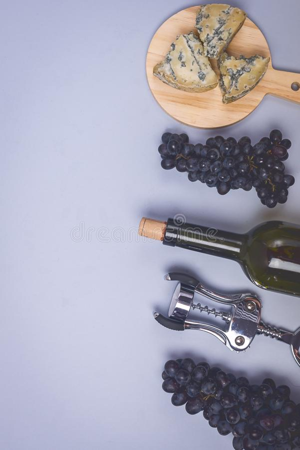 Cheeses on Wooden Board Bottle of Wine Ripe Grape on a Blue Background Top view Flat Lay Copy Space Wine Background Wine Food. Concept Vertical royalty free stock image