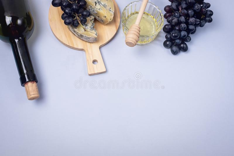 Cheeses on Wooden Board Bottle of Wine Ripe Grape on a Blue Background Top view Flat Lay Copy Space Wine Background Wine Food. Concept royalty free stock photo