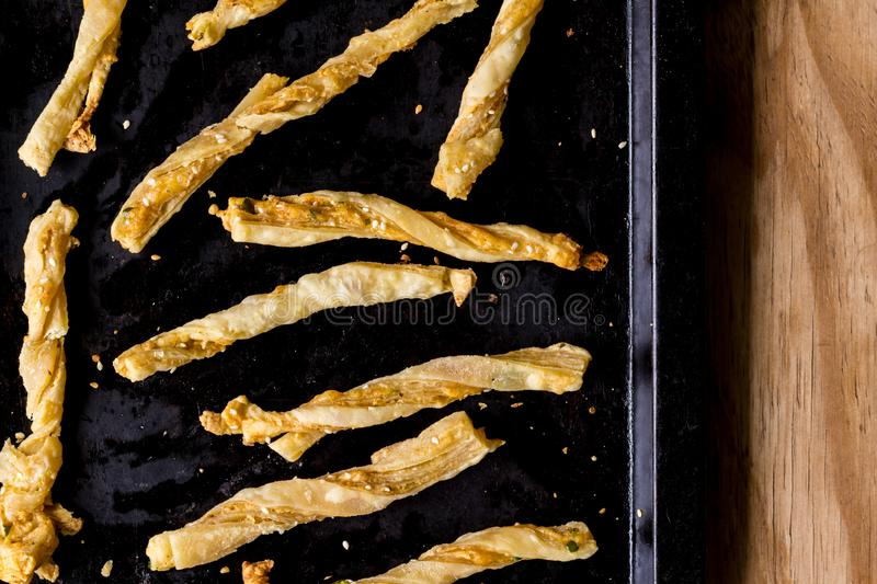 Cheesy cheese pastry straws with sesame seeds and bits of chili in oven pan  - top view photo royalty free stock photos