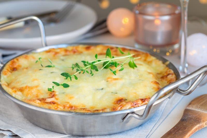 Cheesy scalloped potatoes or potato gratin in a baking dish, holiday theme, horizontal. Cheesy scalloped potatoes or potato gratin in baking dish, holiday theme stock images